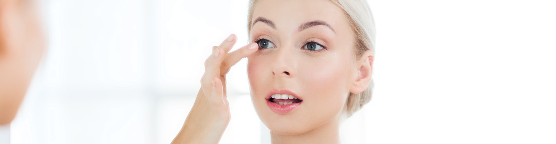 beautiful woman applying contact lense